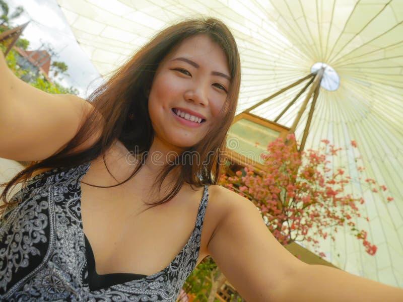 Mujer turística china asiática bonita y feliz joven que sonríe sosteniendo el teléfono móvil o cámara que toma el outd de la imag fotografía de archivo libre de regalías