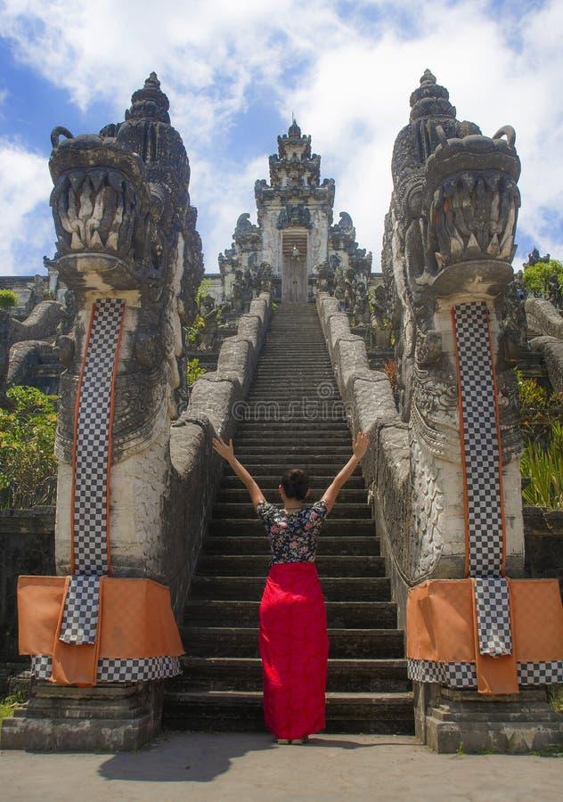 Mujer turística china asiática hermosa joven en sarong que visita el templo hindú hermoso que disfruta de viaje de las vacaciones imágenes de archivo libres de regalías