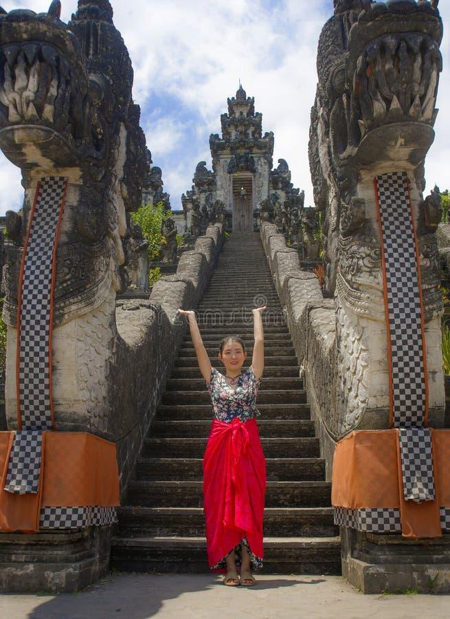 Mujer turística china asiática hermosa joven en sarong que visita el templo hindú hermoso que disfruta de viaje de las vacaciones fotografía de archivo
