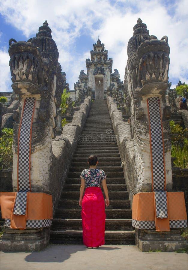 Mujer turística china asiática hermosa joven en sarong que visita el templo hindú hermoso que disfruta de viaje de las vacaciones fotos de archivo libres de regalías