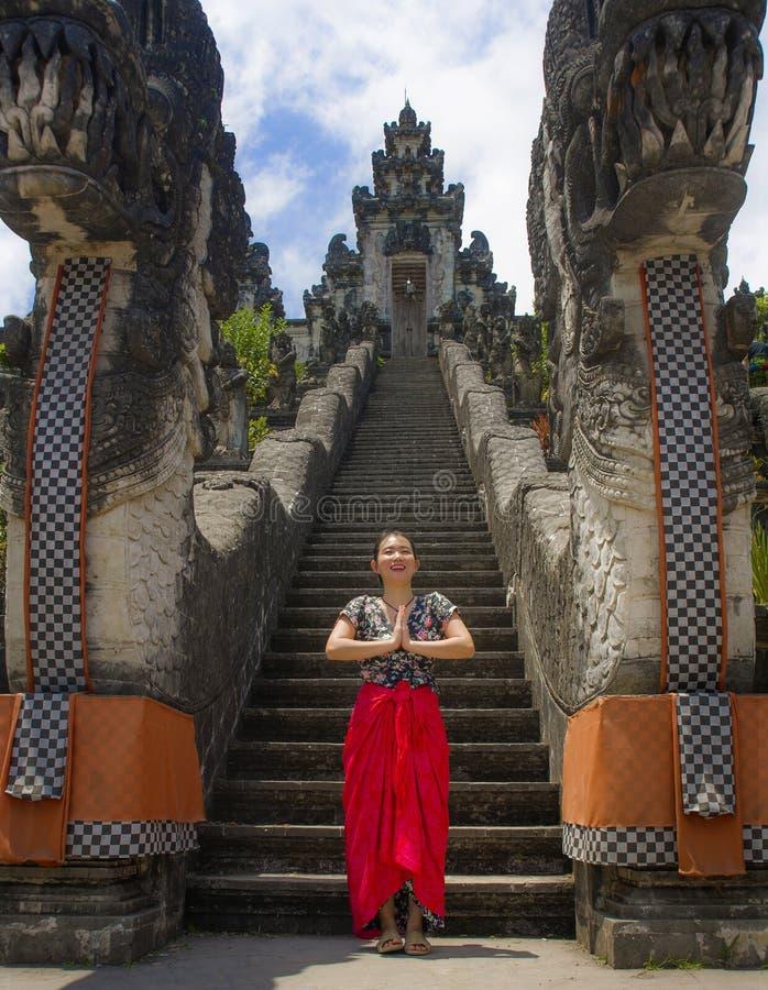 Mujer turística china asiática hermosa joven en sarong que visita el templo hindú hermoso que disfruta de viaje de las vacaciones fotos de archivo