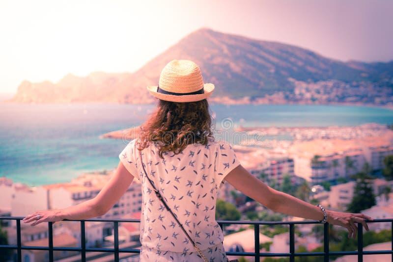 Mujer turística con el sunhat de la paja que mira al mar Mediterráneo en Altea, Alicante, España foto de archivo