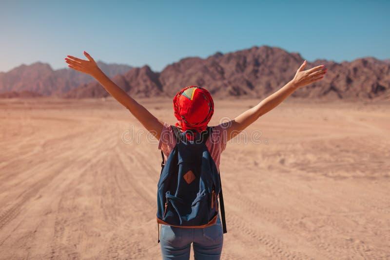 Mujer turística con la bufanda que lleva de la mochila en la cabeza Viajero feliz que admira el desierto y las montañas de Sinaí fotos de archivo libres de regalías