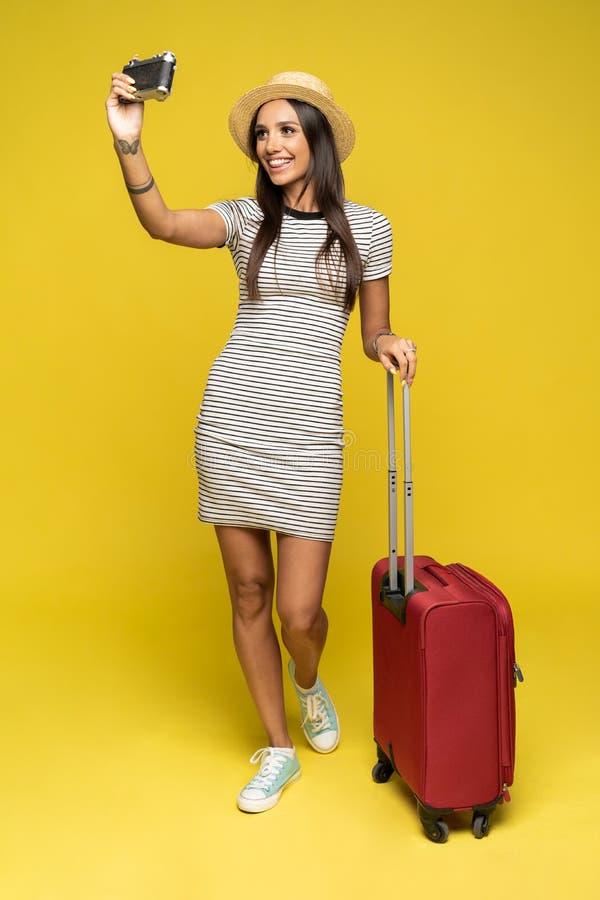 Mujer turística con la maleta en la ropa casual del verano que hace el selfie aislado en fondo amarillo fotos de archivo