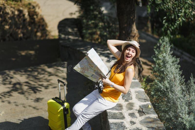 Mujer turística de risa emocionada del viajero en sombrero amarillo de la ropa con el mapa de la ciudad de la tenencia de la male fotos de archivo libres de regalías