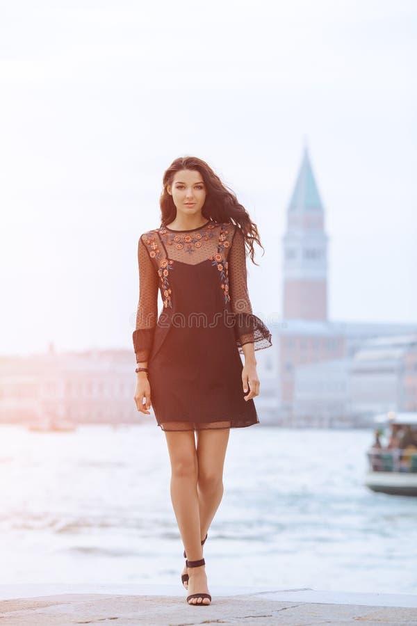Mujer turística del viaje en el embarcadero contra hermosa vista en el chanal veneciano en Venecia, Italia imágenes de archivo libres de regalías
