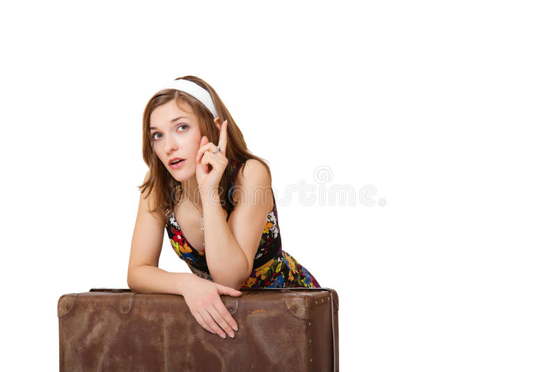 Mujer turística joven feliz que se sienta con el bolso y señalar fotografía de archivo libre de regalías