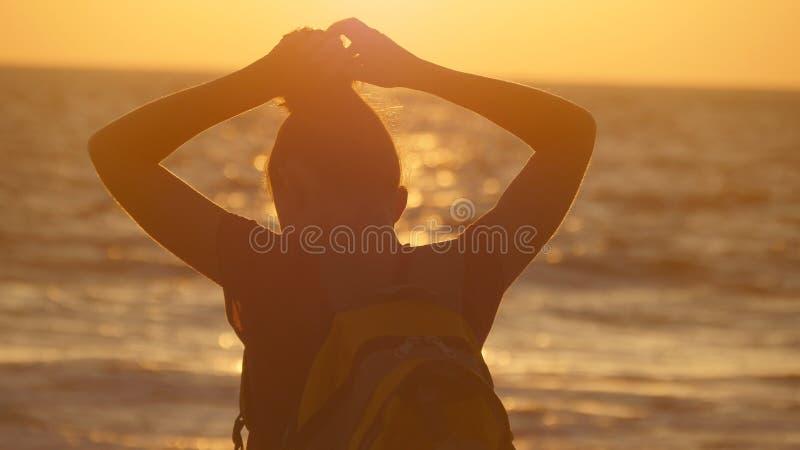 Mujer turística joven que ata la cola de caballo en la playa cerca del mar en la puesta del sol La muchacha hermosa exprime su pe foto de archivo libre de regalías