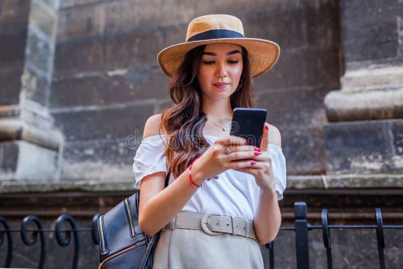 Mujer turística joven que busca para la manera correcta usando smartphone Muchacha elegante del viajero que camina en la calle vi imagenes de archivo