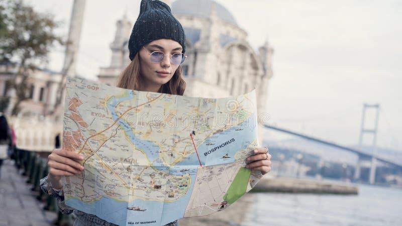 Mujer turística joven que mira el mapa adentro al aire libre imagen de archivo libre de regalías