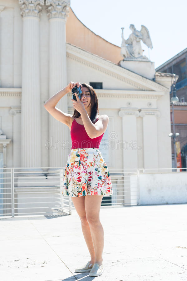 Mujer turística joven que toma la imagen con la cámara del vintage al aire libre imagen de archivo
