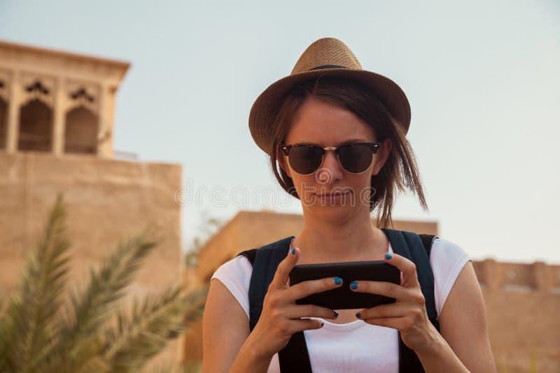 Mujer turística joven que usa el teléfono elegante imagen de archivo