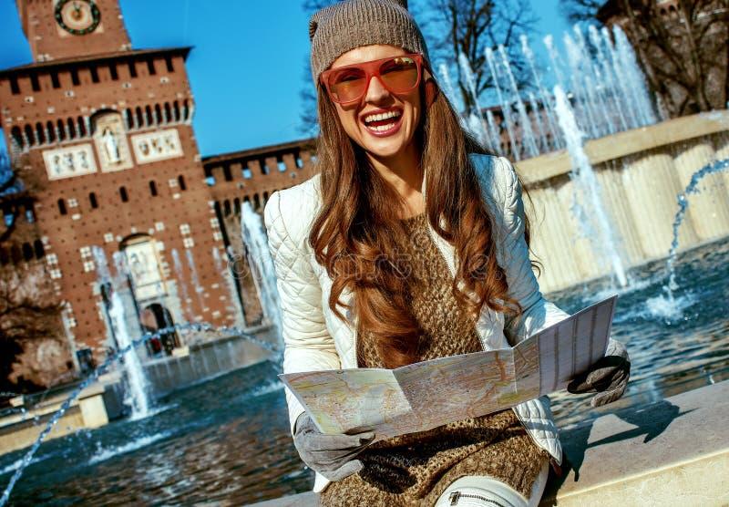 Mujer turística moderna sonriente en Milán, Italia con el mapa fotos de archivo