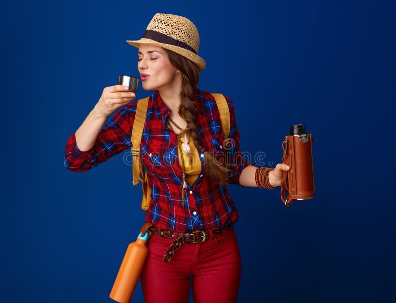 Mujer turística que bebe la bebida caliente de la botella de termo imágenes de archivo libres de regalías