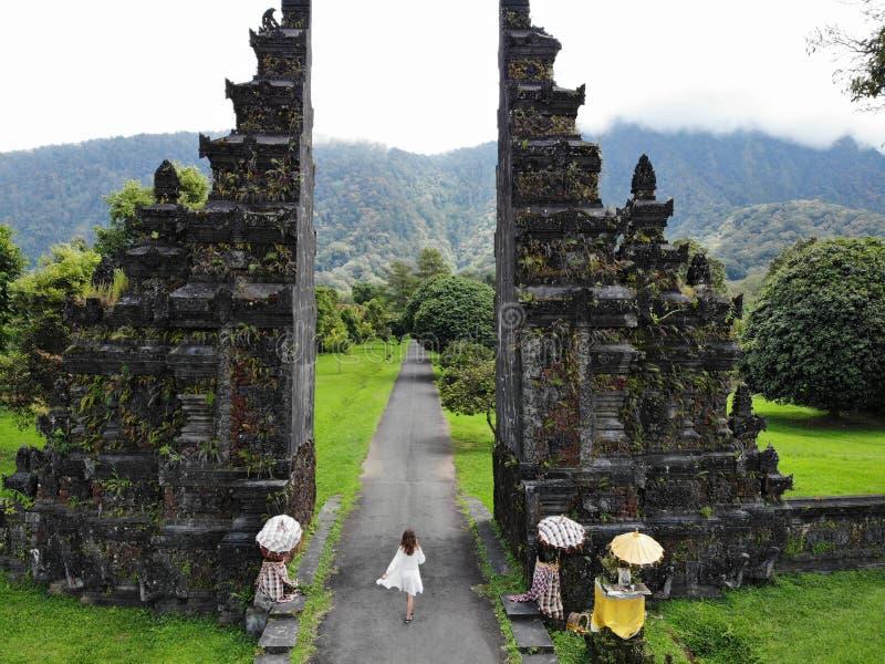 Mujer tur?stica que camina a trav?s de la puerta Candi Bentar del Balinese Vacaciones en Bali fotos de archivo libres de regalías