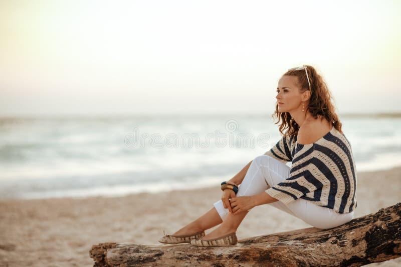 Mujer turística que mira en la distancia mientras que se sienta en la playa fotografía de archivo
