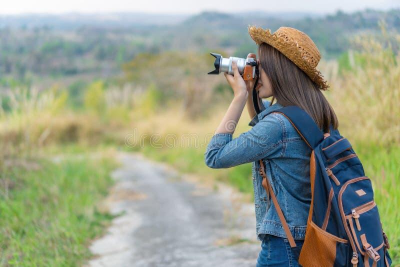 Mujer turística que toma la foto con su cámara en naturaleza foto de archivo libre de regalías