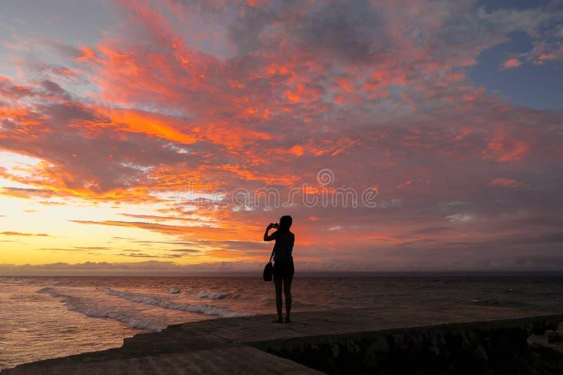 Mujer turística que toma una foto de la puesta del sol fotos de archivo