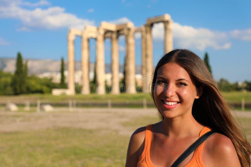 Mujer turística sonriente con el templo griego de Zeus olímpico en el fondo, Atenas, Grecia fotografía de archivo