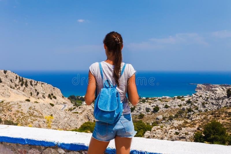 Mujer tur?stica que mira paisaje del mar cerca de Stegna y de Archangelos en la isla de Rodas, Dodecanese, Grecia Panorama con la imagen de archivo