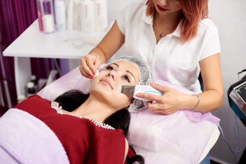 Mujer ultrasónica de la peladura del depurador de la piel en gabinete cosmético foto de archivo