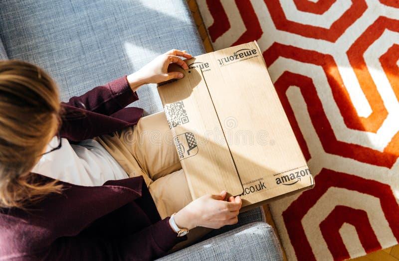 Mujer unboxing desempaquetando el Amazonas r foto de archivo libre de regalías