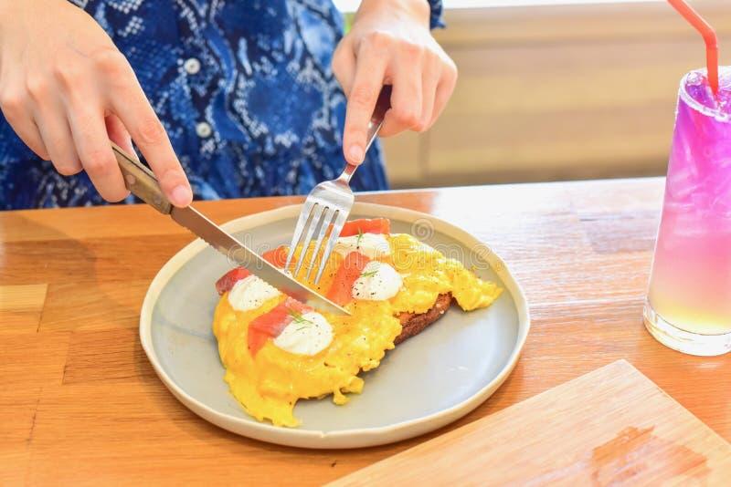 Mujer usando el cuchillo y la bifurcación para comer los huevos revueltos en tostada imagen de archivo