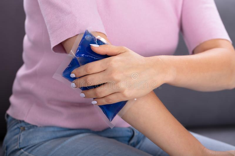 Mujer usando paquete del gel del hielo en el brazo fotos de archivo libres de regalías