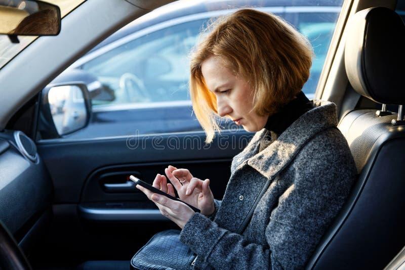 Mujer usando Smartphone en coche fotos de archivo
