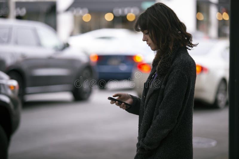 Mujer usando un App de Smartphone que espera un Rideshare foto de archivo libre de regalías