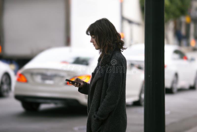 Mujer usando un App de Smartphone que espera un Rideshare fotografía de archivo