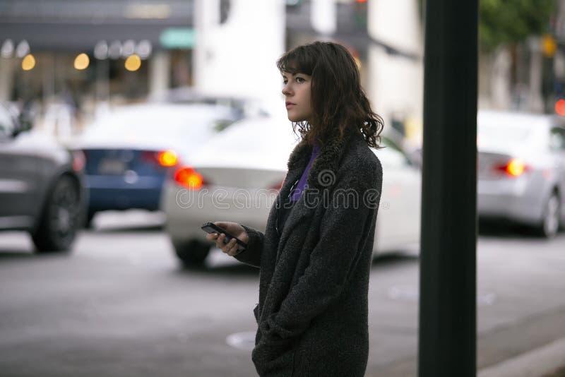 Mujer usando un App de Smartphone que espera un Rideshare imágenes de archivo libres de regalías