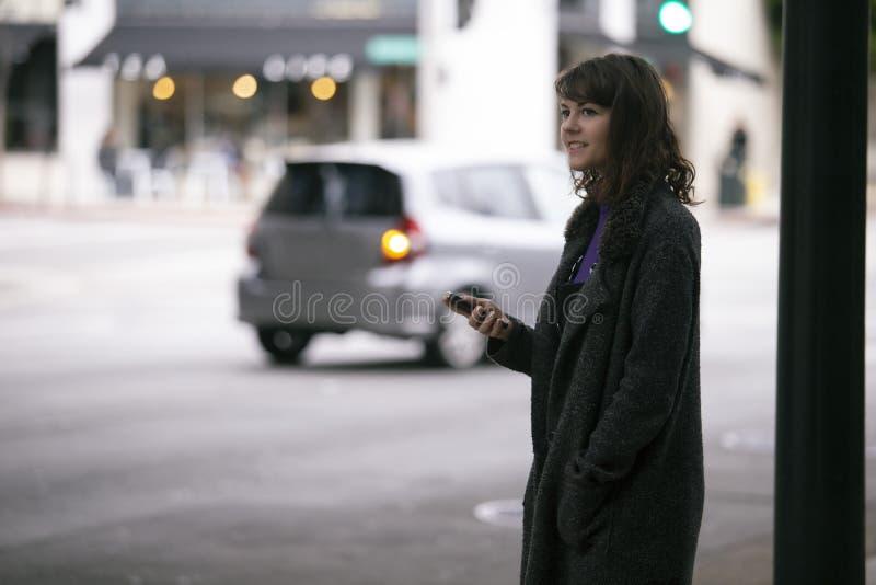 Mujer usando un App de Smartphone que espera un Rideshare imagen de archivo libre de regalías