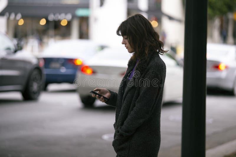 Mujer usando un App de Smartphone que espera un Rideshare foto de archivo