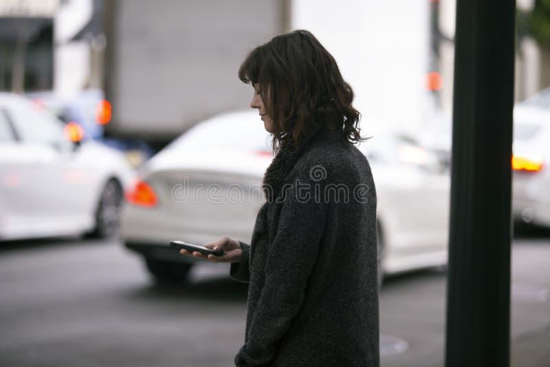 Mujer usando un App de Smartphone que espera un Rideshare imagenes de archivo