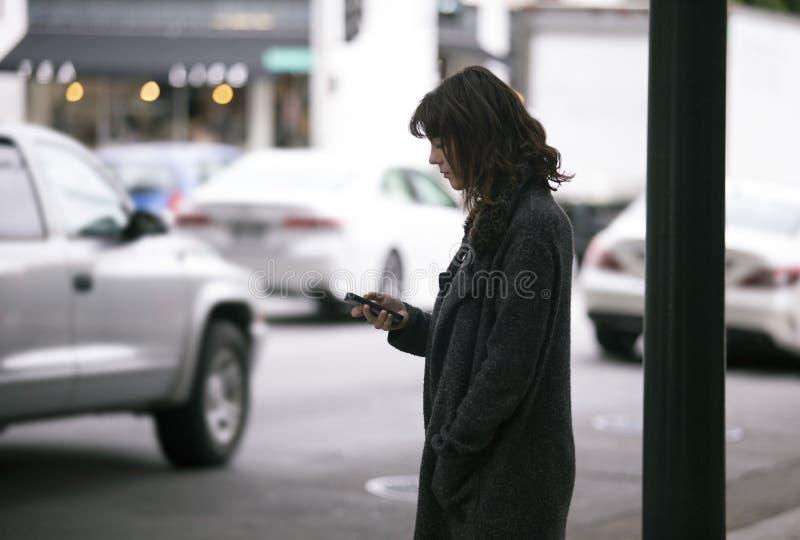Mujer usando un App de Smartphone que espera un Rideshare fotos de archivo libres de regalías