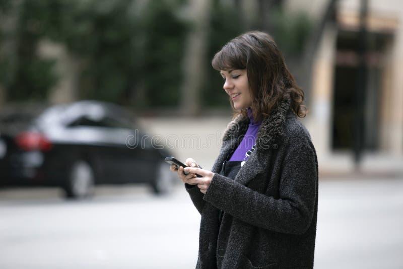 Mujer usando un App del teléfono y para una parte del paseo que espera fotos de archivo libres de regalías