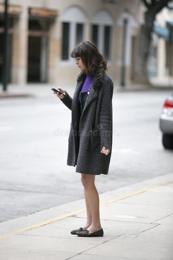 Mujer usando un App del teléfono y para una parte del paseo que espera fotografía de archivo