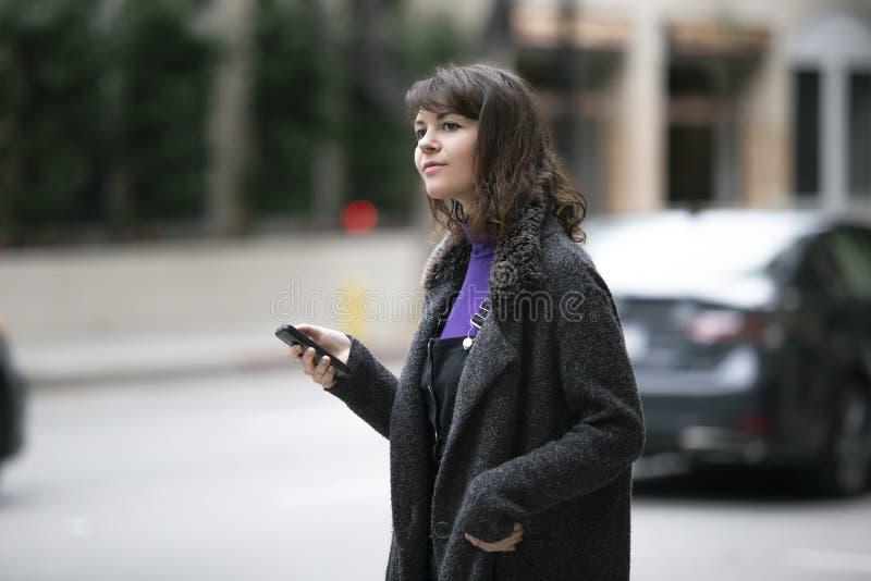 Mujer usando un App del teléfono y para una parte del paseo que espera imagenes de archivo