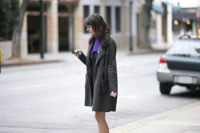Mujer usando un App del teléfono y para una parte del paseo que espera foto de archivo libre de regalías