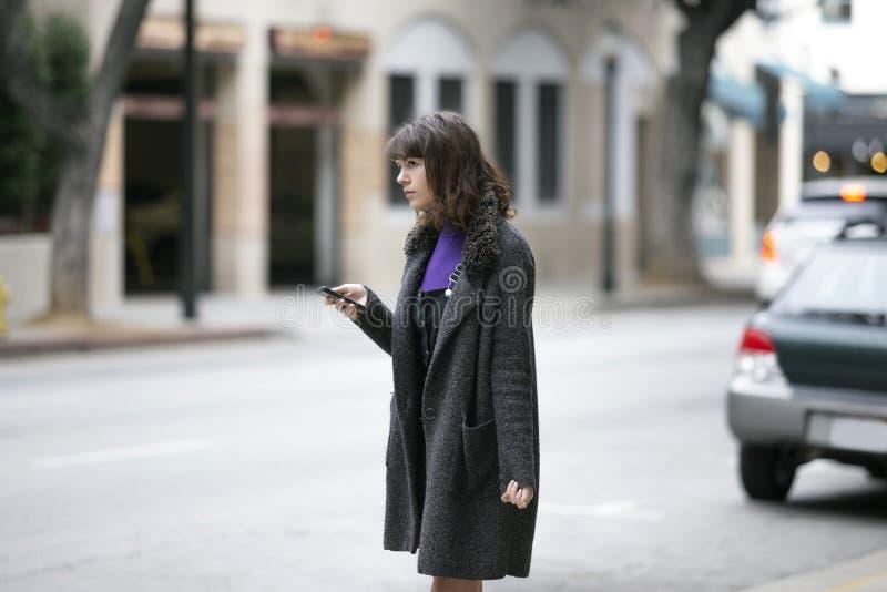 Mujer usando un App del teléfono y para una parte del paseo que espera imagen de archivo libre de regalías