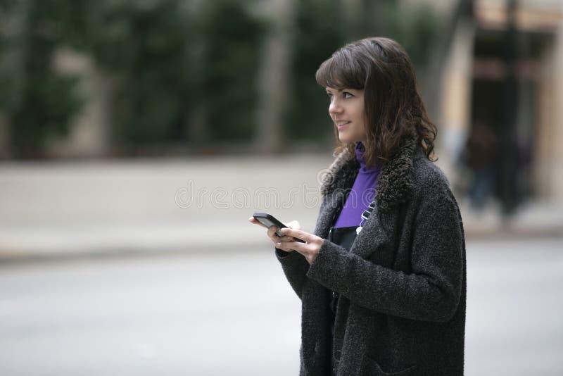 Mujer usando un App del teléfono y para una parte del paseo que espera foto de archivo