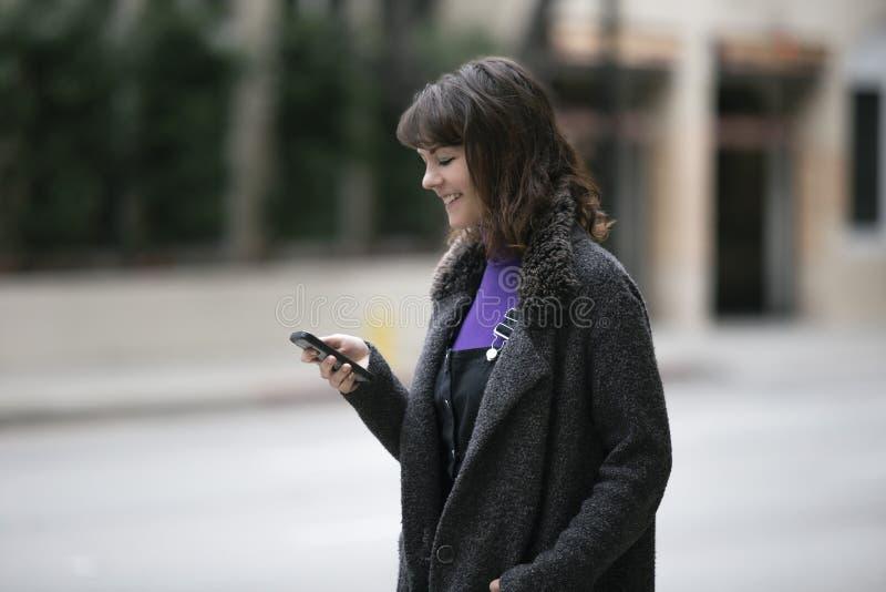 Mujer usando un App del teléfono y para una parte del paseo que espera imagen de archivo