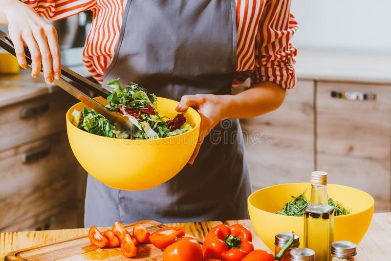 Mujer vegetariana de la forma de vida que cocina la ensalada de mezcla fotografía de archivo