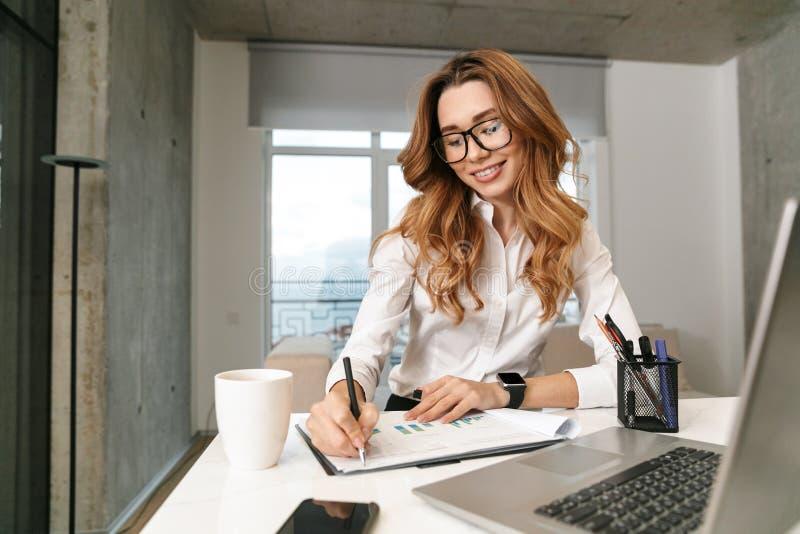 Mujer vestida en camisa formal de la ropa dentro usando el ordenador portátil fotos de archivo