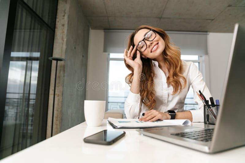 Mujer vestida en camisa formal de la ropa dentro usando el ordenador portátil imagen de archivo libre de regalías