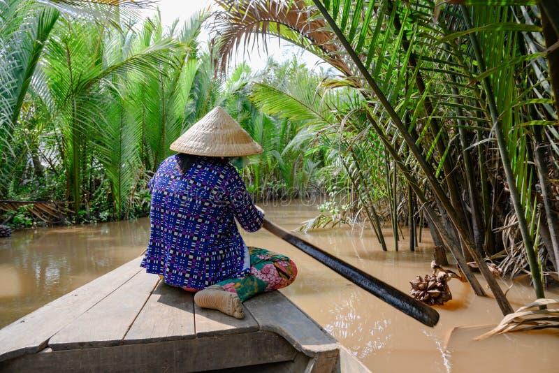 Mujer vietnamita con el sombrero vietnamita que rema un barco de madera a través de la palma en el delta del Mekong, Vietnam de G imagen de archivo libre de regalías