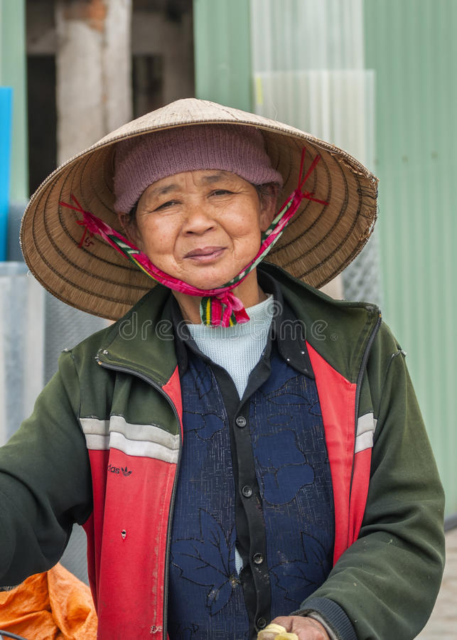 Mujer vietnamita de mediana edad con el sombrero de paja tradicional foto de archivo libre de regalías