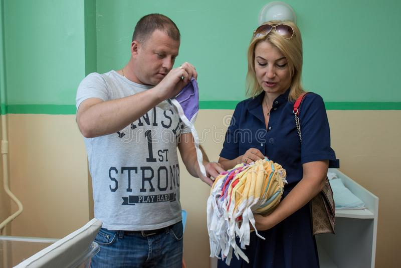 Mujer voluntaria que dona la ropa para los bebés en el hospital de maternidad durante día de la protección de los niños foto de archivo libre de regalías