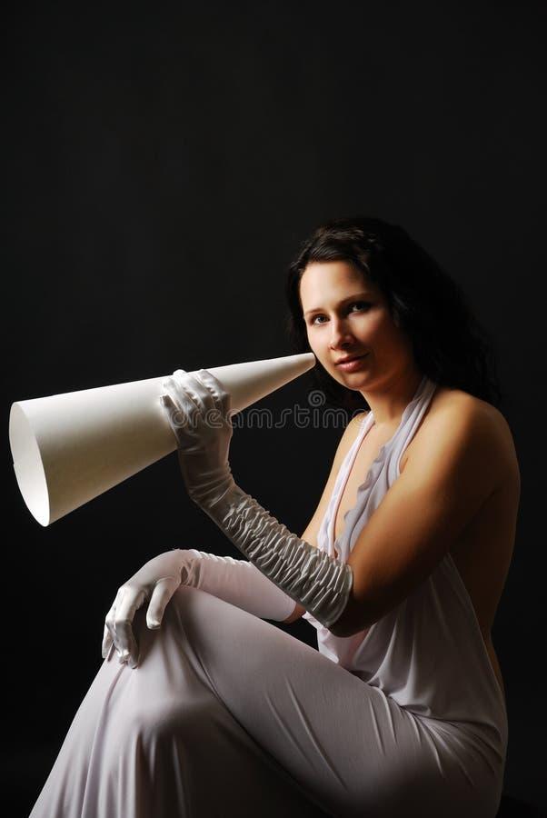 Mujer Well-dressed con el megáfono en la obscuridad. imagenes de archivo